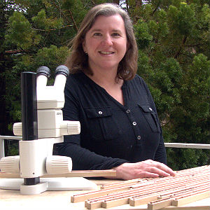 Allison Carroll, standing outdoors with microscope and tree samples