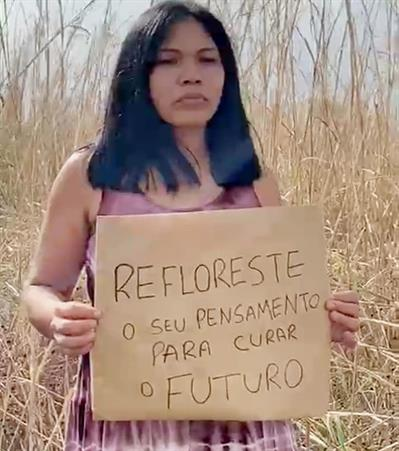 Indigenous woman holding a sign REFLORESTE o seu pensamento para curar o futuro - reforest your thinking to heal the future